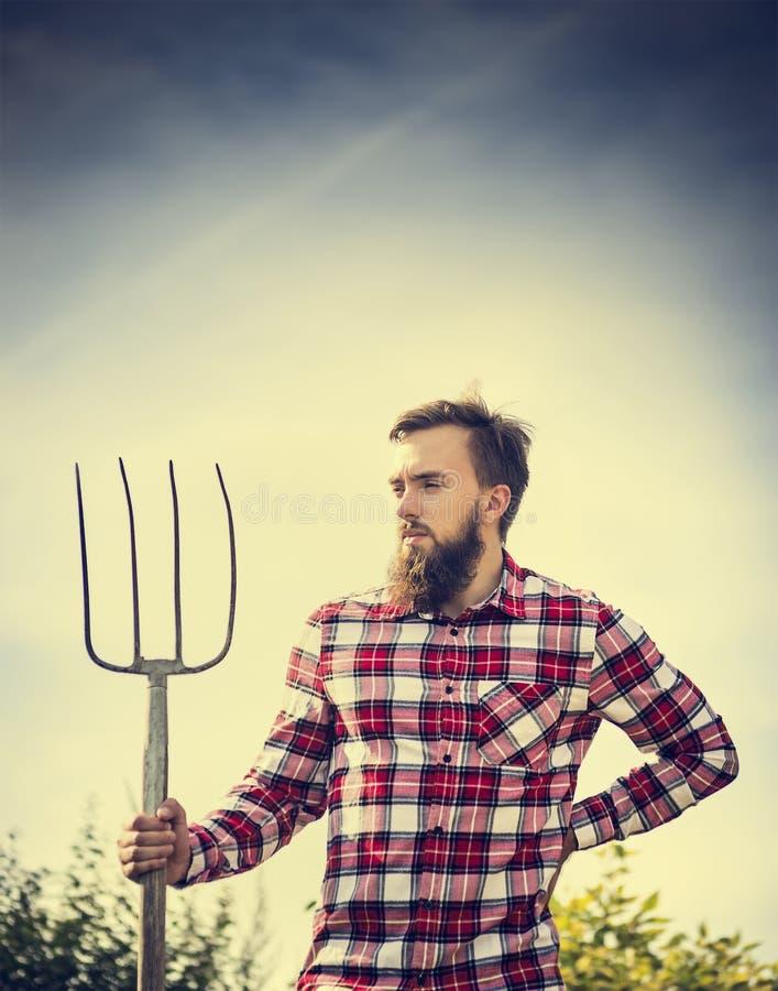 Portrait de jeune agriculteur barbu dans la chemise à carreaux rouge avec la vieille fourche sur le backgrund de nature de ciel,  image stock