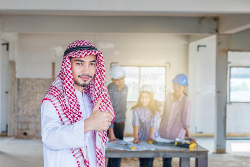 Portrait de jeune Arabe beau avec l'engagement au succès au chantier de construction avec le groupe de fond d'ingénieur image stock