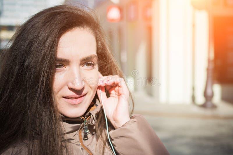 Portrait de jeune belle femme avec la musique de ?coute d'?couteurs rouges photos libres de droits