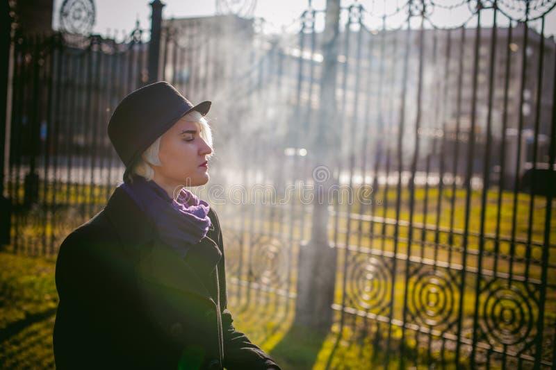 Portrait de jeune belle femme avec les cheveux blancs, dans un manteau noir, une jupe et un chapeau noir, fumant une cigarette él photographie stock libre de droits