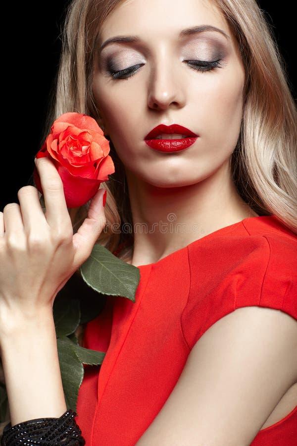 Portrait de jeune belle femme blonde dans la robe rouge avec r rouge image libre de droits