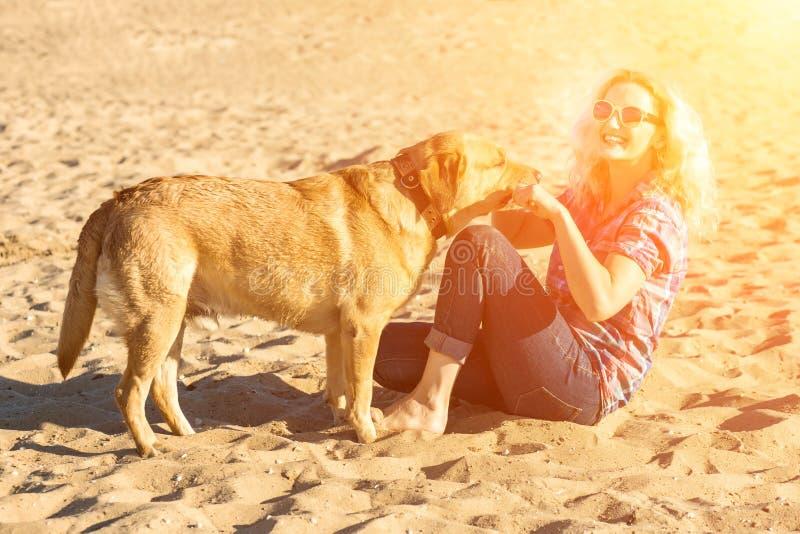 Portrait de jeune belle femme dans des lunettes de soleil se reposant sur la plage de sable étreignant le chien de golden retriev photos stock
