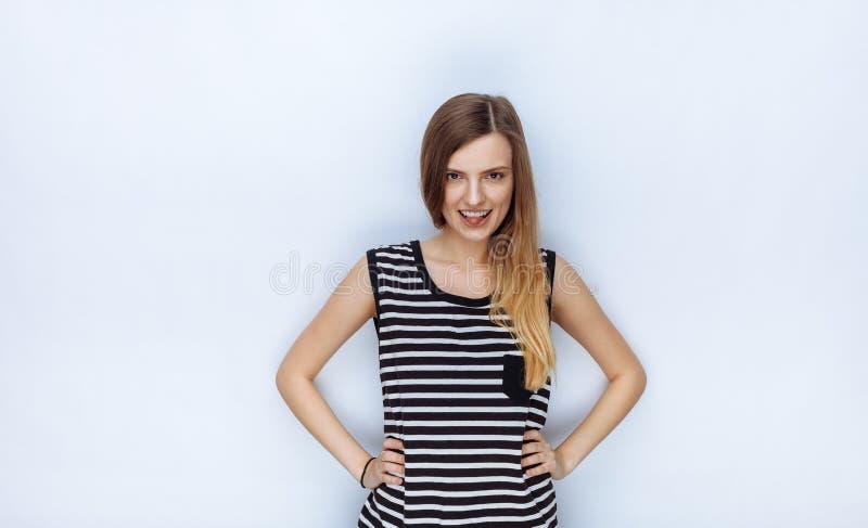 Portrait de jeune belle femme heureuse dans la chemise rayée montrant sa langue posant des mains sur des hanches pour les essais  photos stock