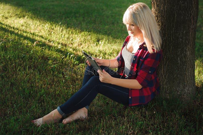 Portrait de jeune belle femme de sourire avec le PC de comprimé, dehors image libre de droits