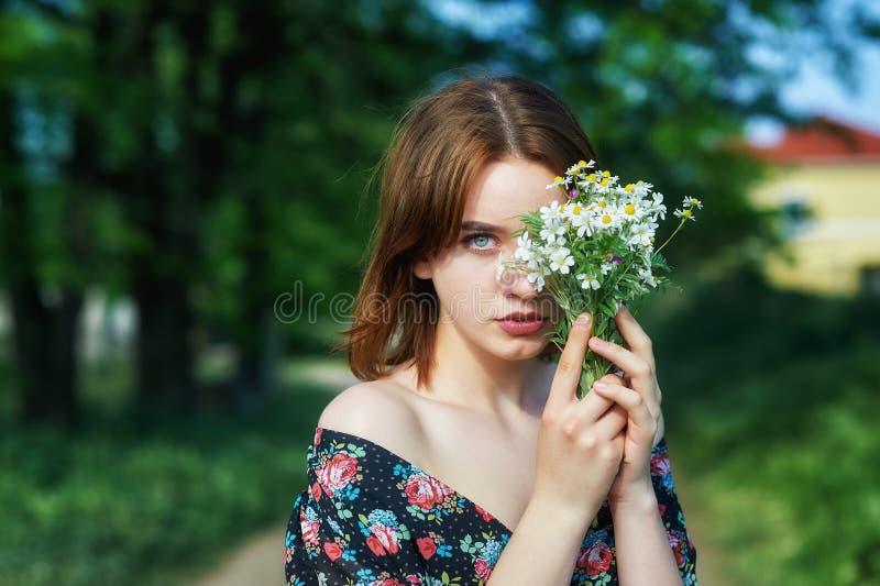 Portrait de jeune belle fille avec des fleurs dehors photos stock