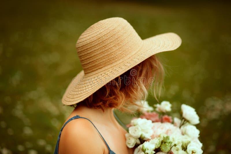Portrait de jeune belle fille avec les cheveux bouclés du dos en fleurs de keepings de chapeau d'été ?t? photographie stock