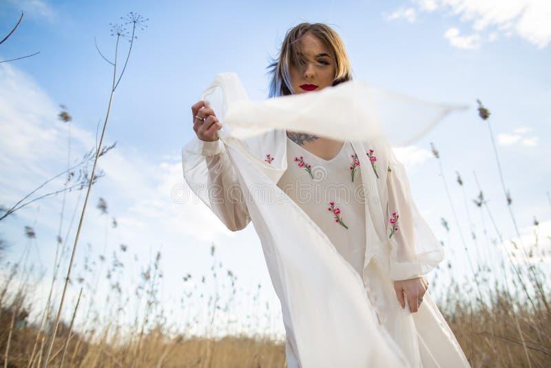 Portrait de jeune belle fille dans la robe blanche dans le domaine de blé, marche, insouciante Apprécier le beau jour ensoleillé photo libre de droits