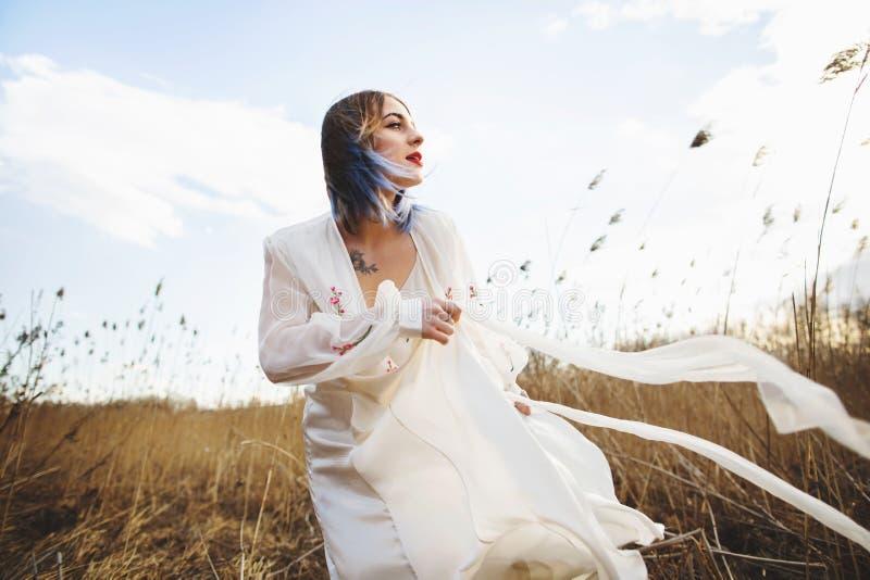 Portrait de jeune belle fille dans la robe blanche dans le domaine de bl?, marche, insouciante Appr?cier le beau jour ensoleill? images libres de droits