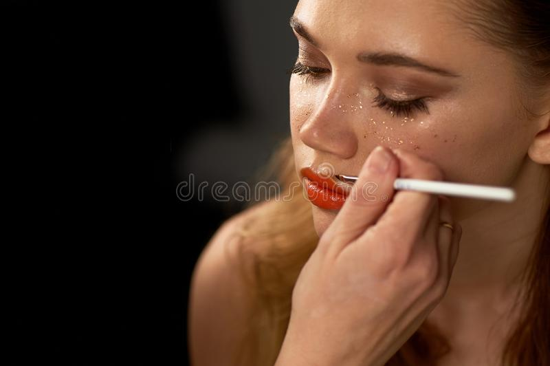 Portrait de jeune belle fille dans le studio, avec le maquillage professionnel Tir de beauté Le maquilleur peint ses lèvres avec photo stock