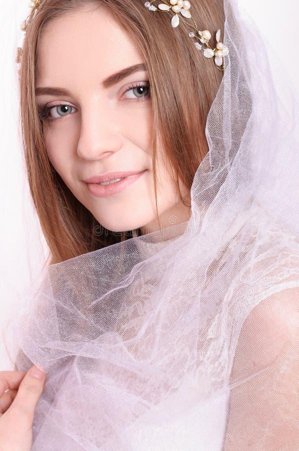 Portrait de jeune belle jeune mariée avec le sourire blanc de voile photographie stock libre de droits