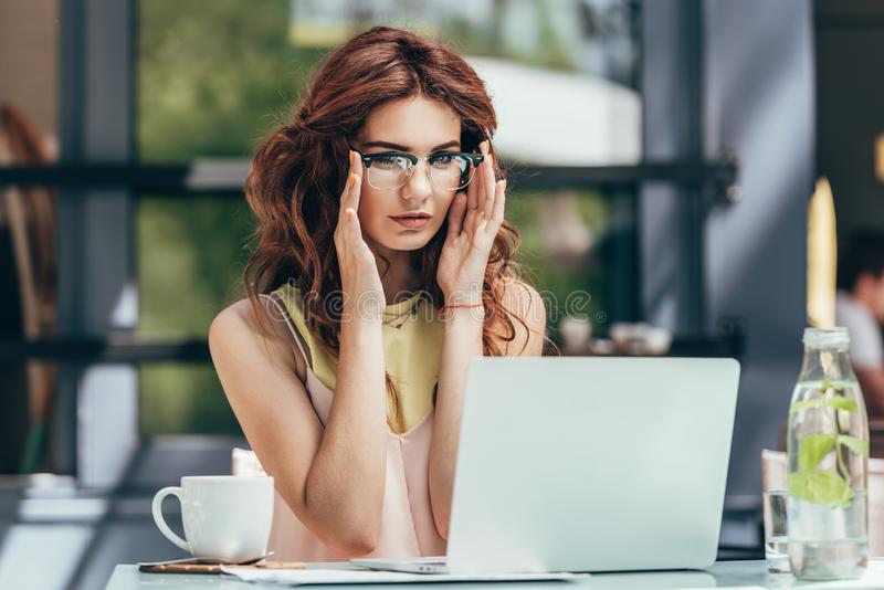 portrait de jeune blogger dans des lunettes travaillant sur l'ordinateur portable photographie stock
