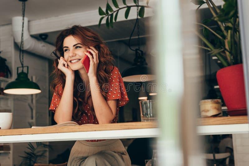 portrait de jeune blogger parlant sur le smartphone à la table avec le carnet images stock