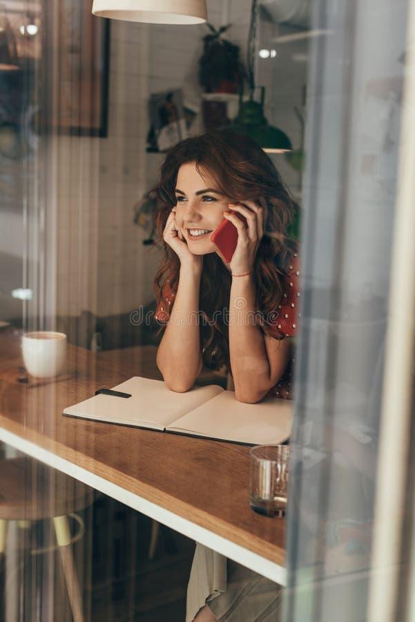portrait de jeune blogger parlant sur le smartphone à la table avec le carnet image libre de droits
