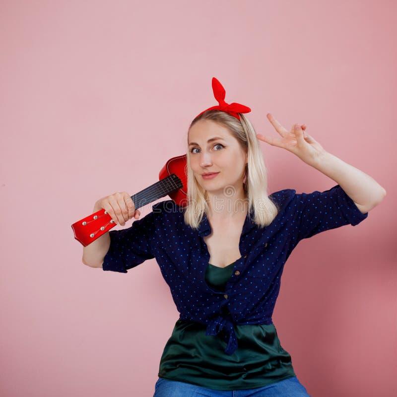 Portrait de jeune blonde élégante avec l'ukulélé Une femme avec un bandeau sur un fond rose photographie stock libre de droits