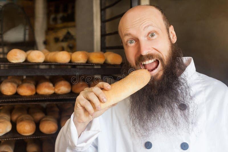 Portrait de jeune boulanger affamé adulte heureux avec la longue barbe dans la position uniforme blanche dans son lieu de travail photo libre de droits