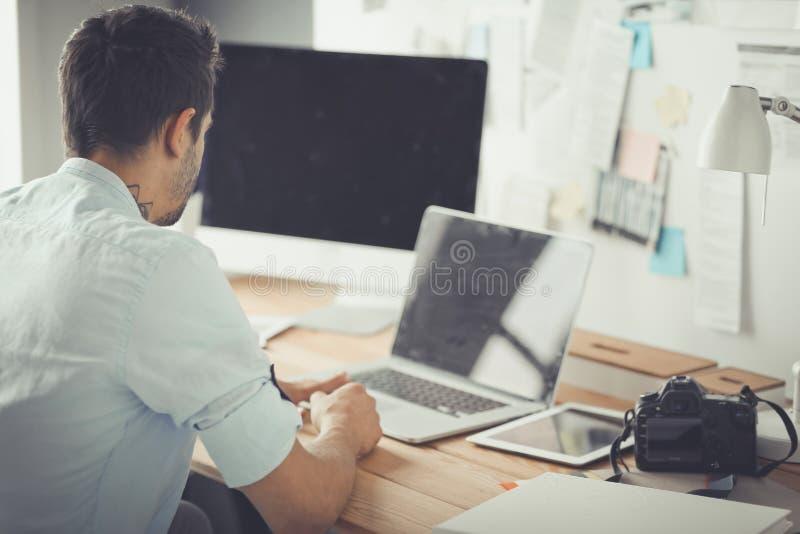 Portrait de jeune concepteur se reposant au studio graphique devant l'ordinateur portable et l'ordinateur tout en travaillant en  photo stock