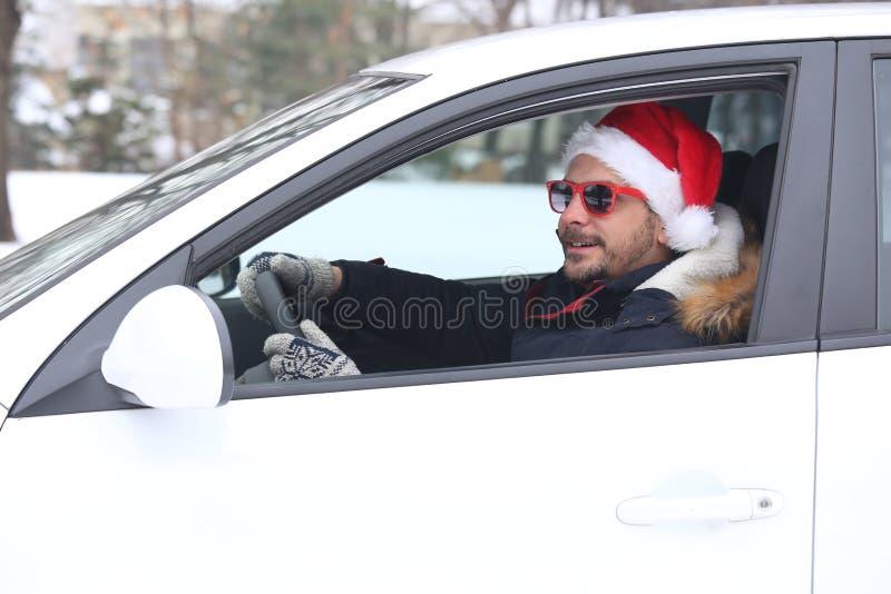 Portrait de jeune conducteur de voiture avec le chapeau de Santa appréciant la neige photo libre de droits