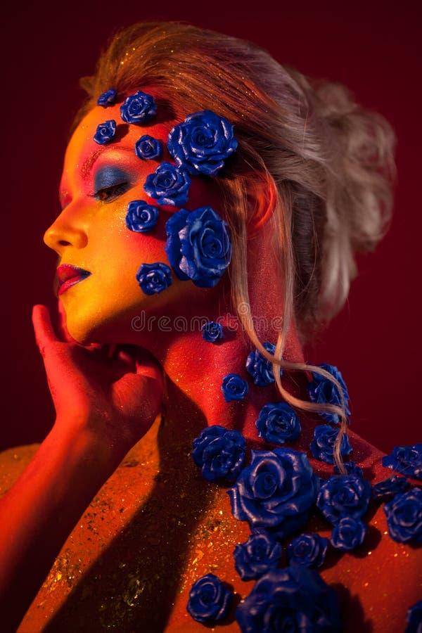 Portrait de jeune et attirante femme avec le maquillage d'art Couleurs ardentes, scintillement sur le visage et décoration floral photo libre de droits