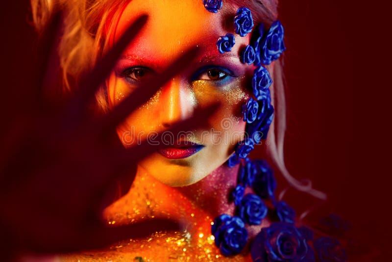 Portrait de jeune et attirante femme avec le maquillage d'art Couleurs ardentes, scintillement sur le visage et décoration floral photographie stock libre de droits