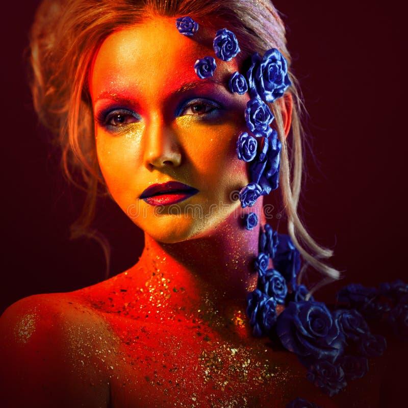 Portrait de jeune et attirante femme avec le maquillage d'art Couleurs ardentes, scintillement sur le visage et décoration floral photos libres de droits
