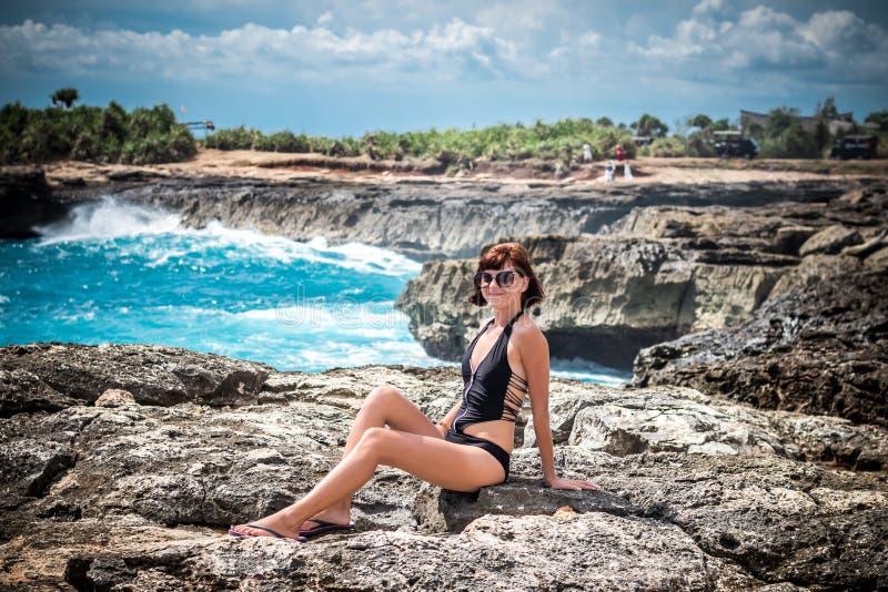Portrait de jeune et sexy femme sur les roches près de l'océan sauvage Tempête, vagues énormes venant et éclaboussant tropical photo stock