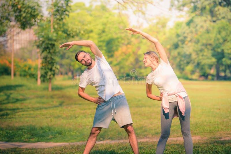 Portrait de jeune exercice de couples pour la sant? en parc au coucher du soleil Sport et amour de concept Ton chaud photographie stock