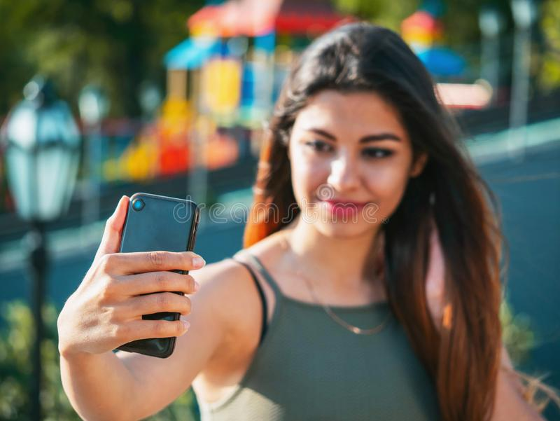 Portrait de jeune femelle attirante dans l'équipement de mode rendant le selfie extérieur tout en se reposant sur des escaliers B images libres de droits