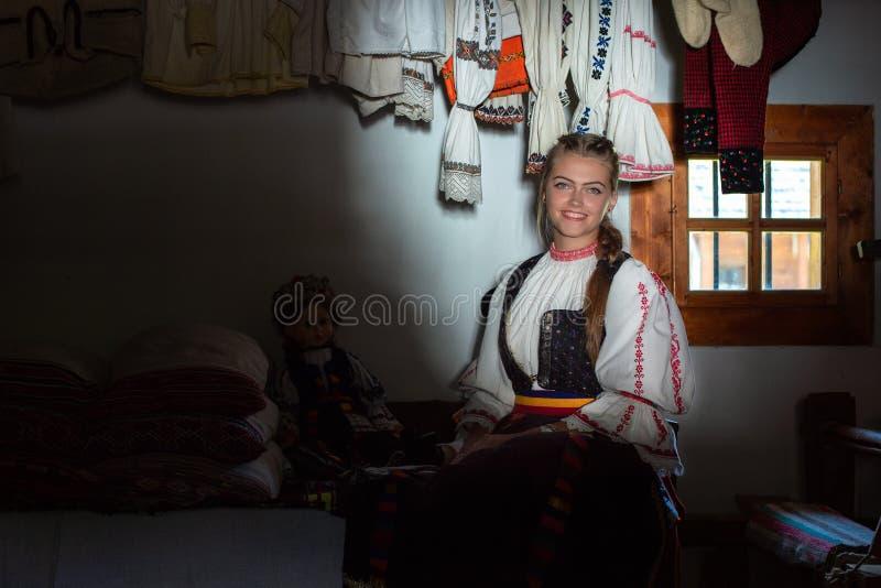 Portrait de jeune femme à l'intérieur de maison traditionnelle avec le costume traditionnel roumain photo stock