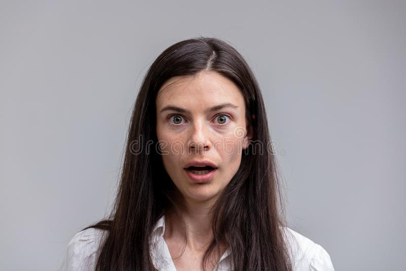 Portrait de jeune femme étonnée aux cheveux longs images stock