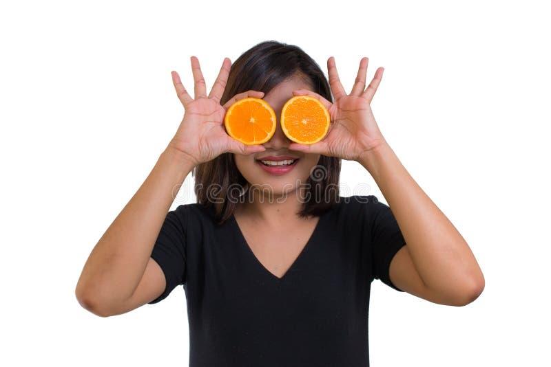 Portrait de jeune femme asiatique tenant les tranches oranges devant ses yeux et sourire d'isolement sur le fond blanc photographie stock