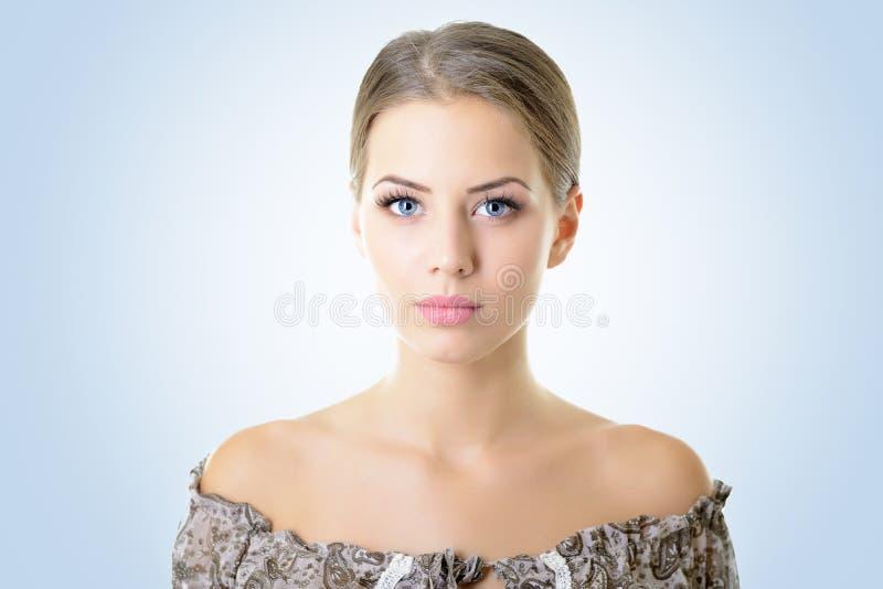 Portrait de jeune femme attirante au-dessus de bleu photographie stock libre de droits