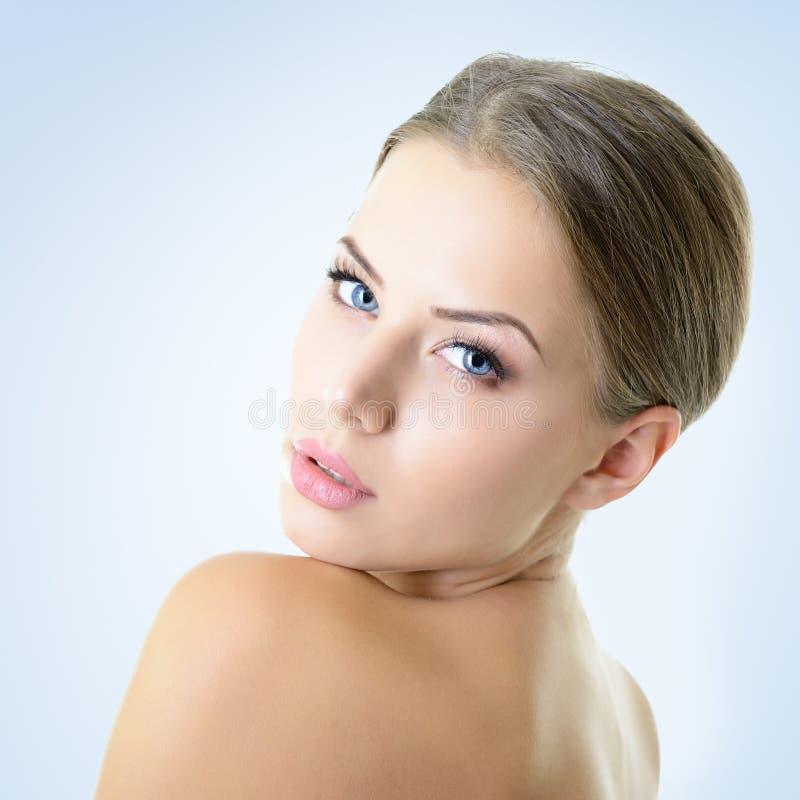 Portrait de jeune femme attirante au-dessus de fond bleu photo libre de droits