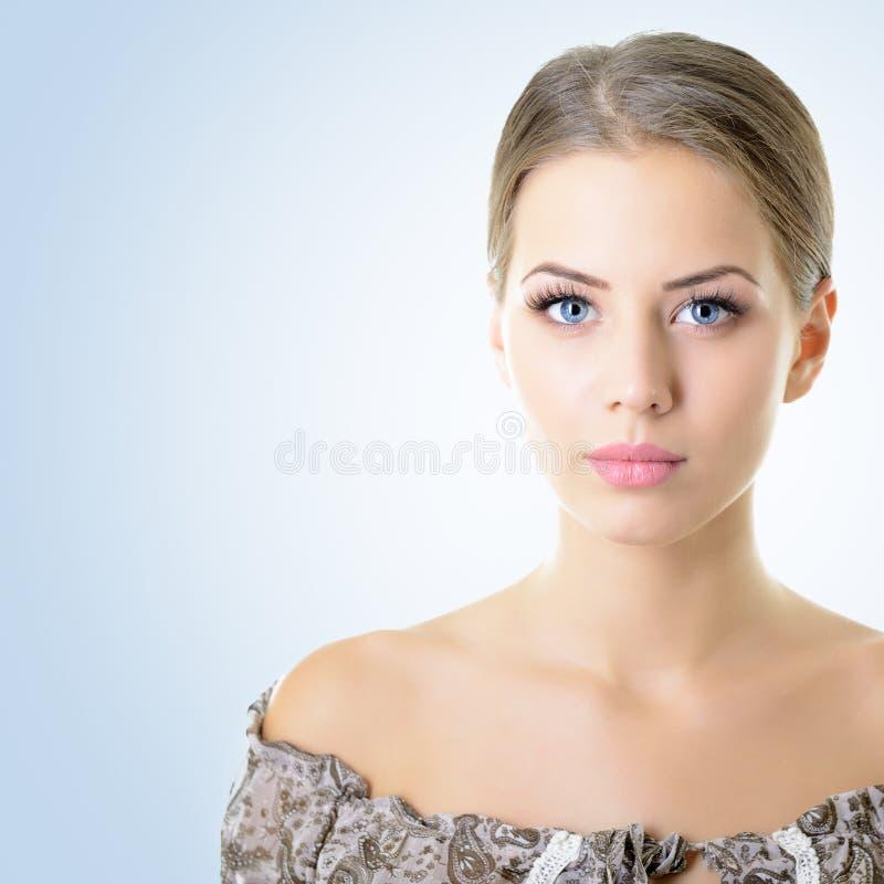 Portrait de jeune femme attirante plus d'au-dessus du bleu image stock
