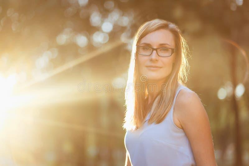 Portrait de jeune femme avec des verres dans le contre-jour photographie stock