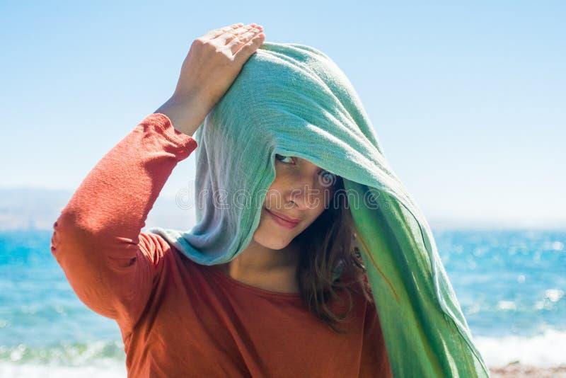 Portrait de jeune femme avec l'écharpe de long vert sur la tête sur la plage avec le fond de mer photographie stock