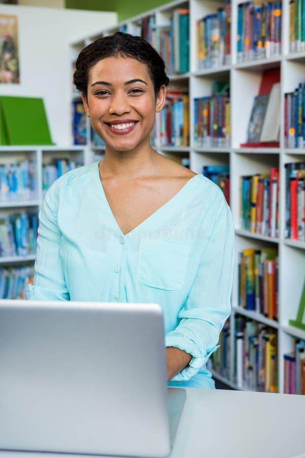 Portrait de jeune femme avec l'ordinateur portable dans la bibliothèque image stock