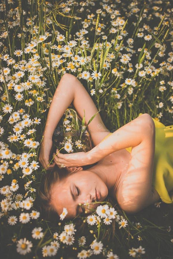 Portrait de jeune femme avec la peau propre rayonnante se couchant parmi des fleurs sur un beau pré photos stock