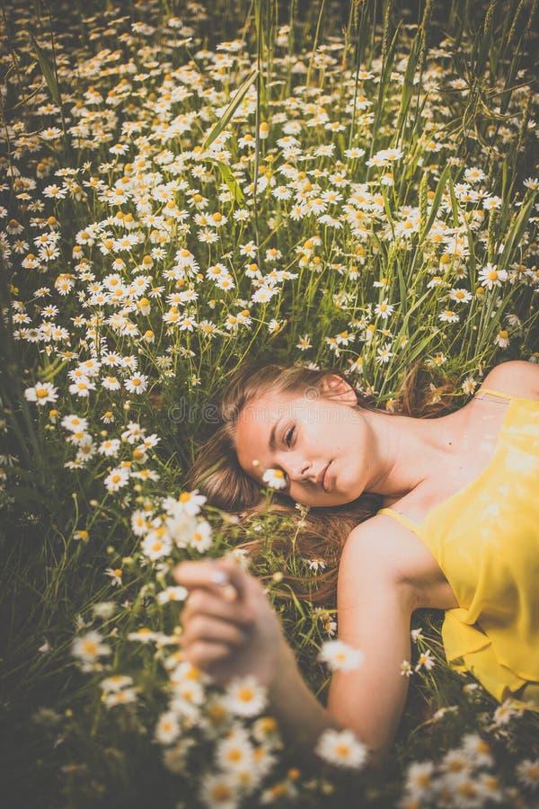 Portrait de jeune femme avec la peau propre rayonnante se couchant parmi des fleurs sur un beau pré images stock