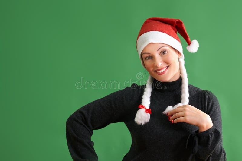 Portrait de jeune femme avec le chapeau du père noël se tenant sur le fond vert photos stock