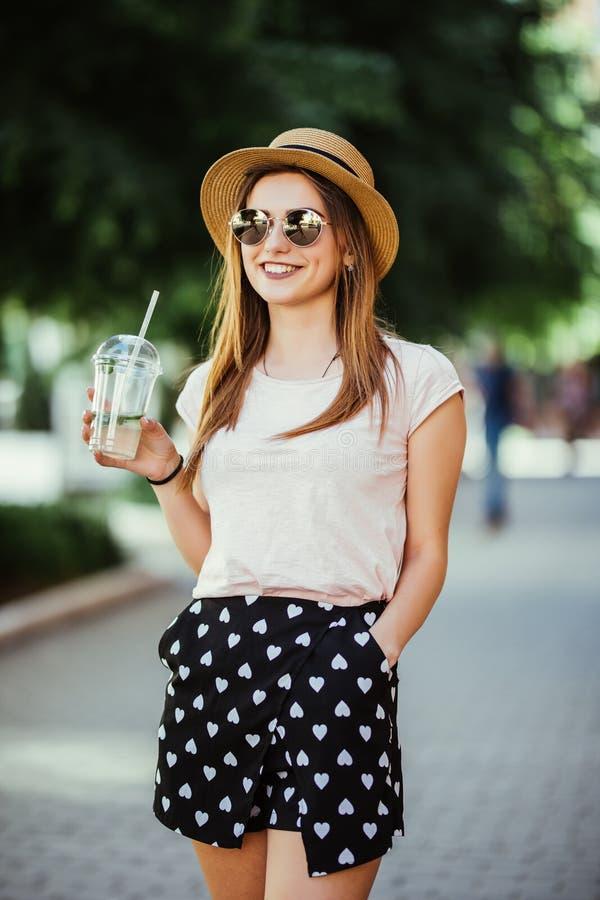 Portrait de jeune femme avec le mojito se reposant l'été de rue de ville photos stock