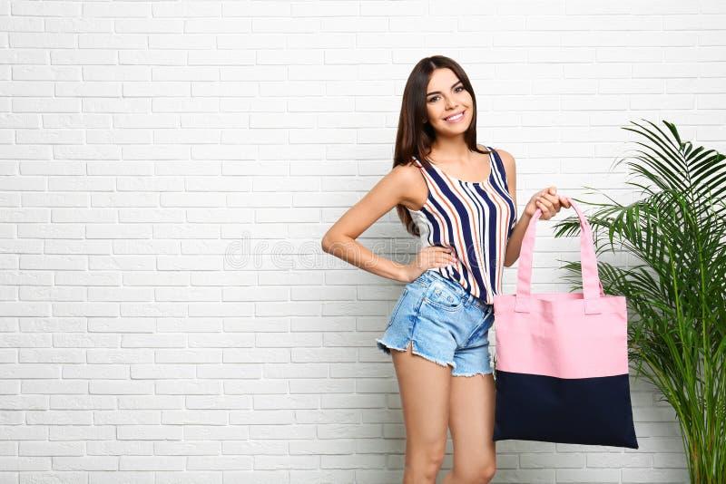 Portrait de jeune femme avec le sac de textile près du mur de briques blanc images stock