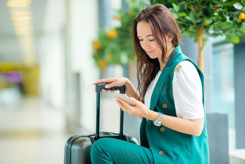 Portrait de jeune femme avec le smartphone dans l'aéroport international Passager de ligne aérienne dans un salon d'aéroport atte photos libres de droits