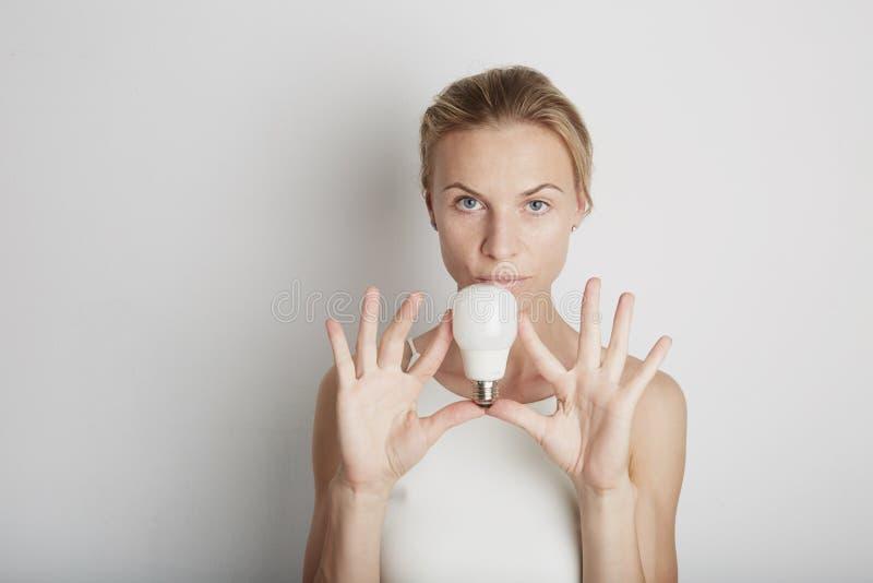 Portrait de jeune femme avec les écouteurs blancs et la lumière électrique avec le fond vide photos libres de droits