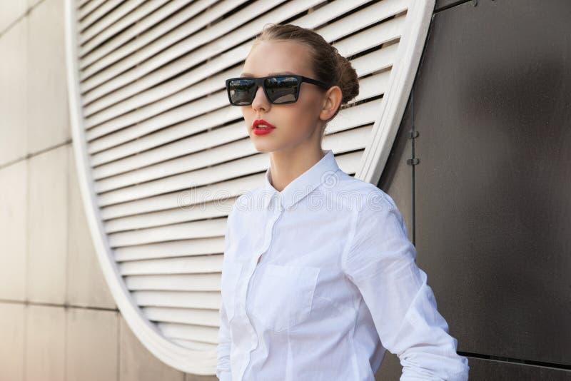 Portrait de jeune femme avec les lèvres rouges dans des lunettes de soleil regardant loin photos stock