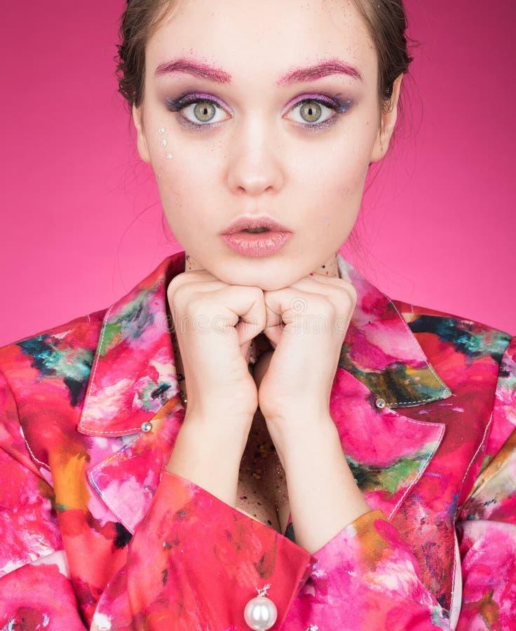 Portrait de jeune femme bien disposée dans une veste colorée lumineuse Maquillage avec le scintillement photographie stock libre de droits