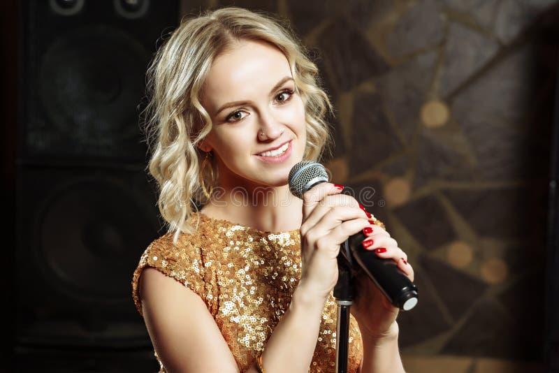 Portrait de jeune femme blonde avec le microphone sur le fond foncé photographie stock
