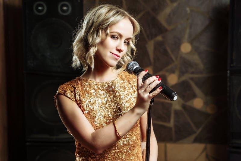 Portrait de jeune femme blonde avec le microphone sur le fond foncé images libres de droits