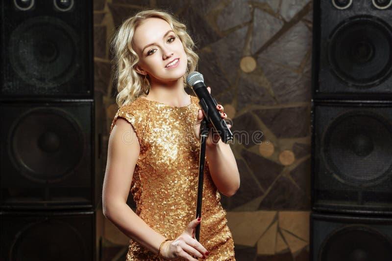 Portrait de jeune femme blonde avec le microphone sur le fond foncé photos stock