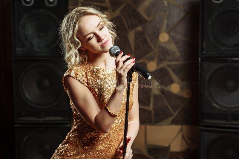 Portrait de jeune femme blonde avec le microphone sur le fond foncé photo stock