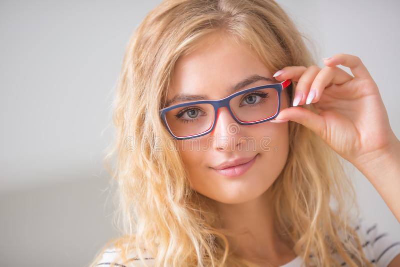 Portrait de jeune femme blonde en verres photo stock